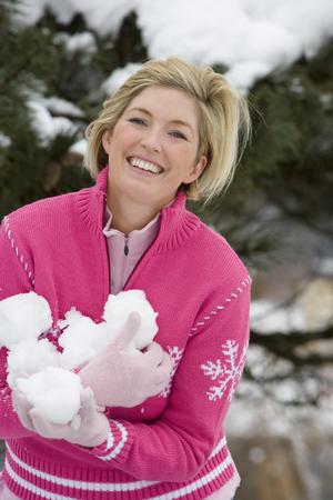 Happy mid adult woman holding snowballs