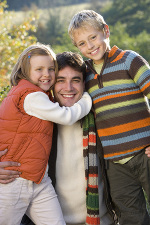 Portrait of father embracing children