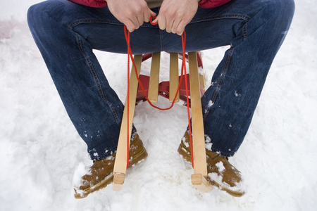 Mid adult man sitting on sled in snow, cropped view