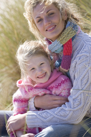 Portrait of mother sitting with daughter on beach Stock Photo