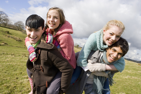 Couples piggybacking in sunny, rural field
