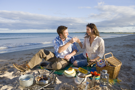 Couple toasting champagne on beach Stock Photo