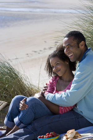 Couple sitting on beach, side view Stock Photo