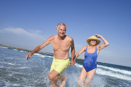 Senior couple walking in sea
