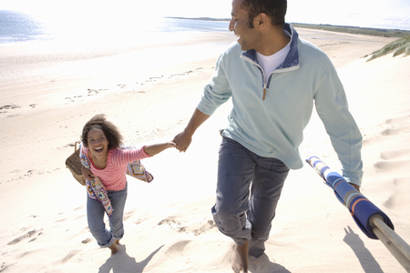 Father and daughter walking on beach, elevated view