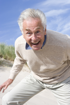 Portrait of senior man shouting on beach Stock Photo