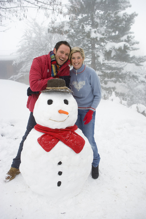 Portrait of mid adult couple with snowman Stock Photo