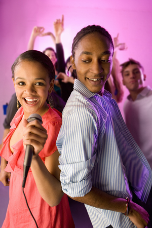 Friends with microphone dancing and singing at nightclub