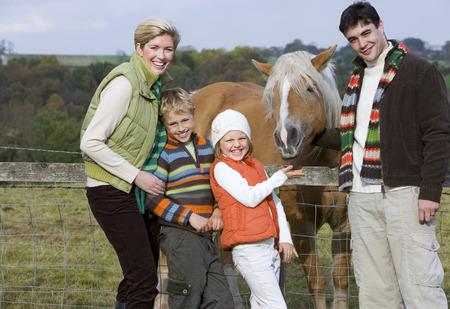 Portrait of family standing near horse Stock Photo