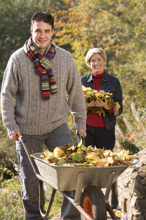 Portrait of young man pushing wheelbarrow, woman carrying leaves in background Stock Photo