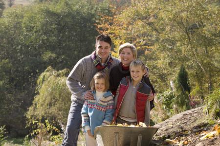 Portrait of family near wheelbarrow Stock Photo