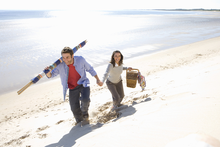 Couple carrying picnic basket and blankets on beach