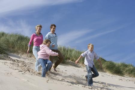 Family running down sand on beach