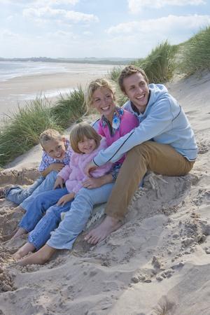 Family sitting on beach Stock Photo