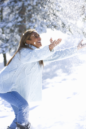 Young woman playing in the snow
