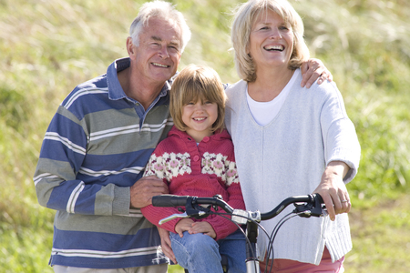 Grandparents with granddaughter sitting on bicycle