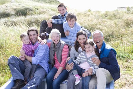 Family sitting in boat, smiling, portrait