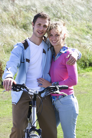 Portrait of young couple with bicycle