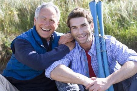Portrait of two men holding oars on beach