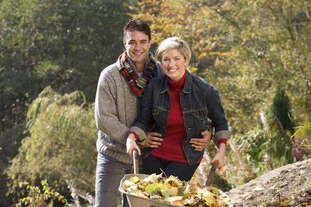 Portrait of couple, woman pushing wheelbarrow, man embracing