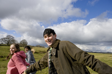 Happy friends holding hands in sunny, rural field Stok Fotoğraf