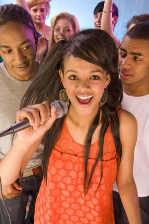 People dancing behind woman singing into microphone