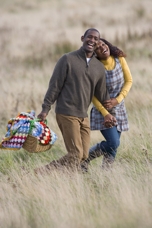 Happy couple with picnic basket holding hands in field