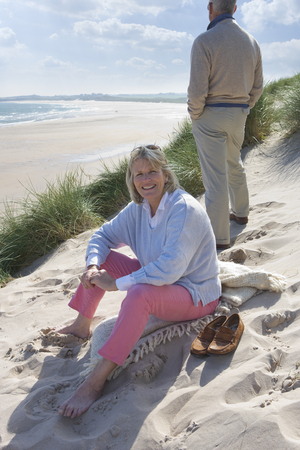Mature woman sitting on beach, man standing in background