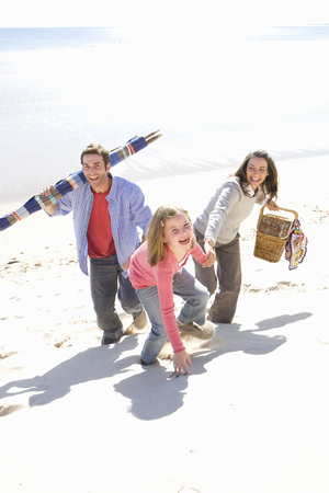 Parents with daughter walking on beach Stock Photo