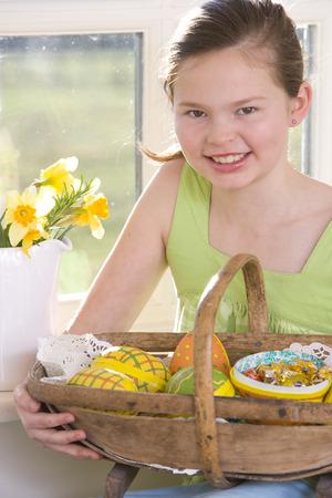 Happy girl holding basket of wooden Easter eggs
