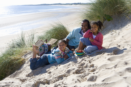 Portrait of father sitting with daughters on beach