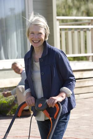 Portrait of senior woman holding mower in garden, man in background Stock Photo