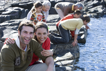Mid adult couple sitting on rock, family in background