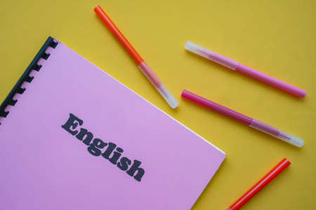 English language workbook with pencils on yellow background. school concept. first September. back to school