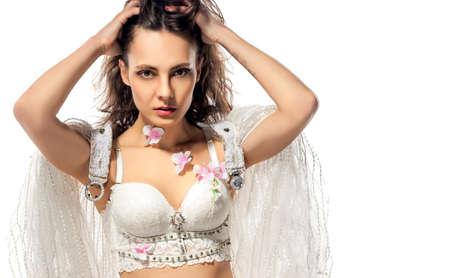 Slim girl in white underwear on the white background. Designer handmade underwear. Model posing in luxurious underwear. Surprised girl.