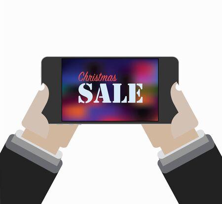 携帯電話の画面上のクリスマス セール。手は、携帯電話を保持しています。
