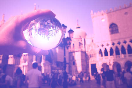This picture was taken in the afternoon at St Marks Square, Venice, Veneto, northeastern Italy. It was spring. It is a portrays to a perfectly transparent glass ball reflecting an upside down image of some of St Marks Square, and monuments (part of Doge  ,  s Palace, and St. Marks Basilica, respectively). Stock Photo