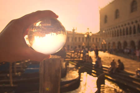 This picture was taken at St Marks Square, Venice, Veneto, northeastern Italy. Sunset was coming. It was spring. The portrays a hand holding a transparent glass ball reflecting an upside down image of some of St Marks Square, the monuments of Partes Doges Palace, National Library of St Mark  ,  s, respectively) and the Grand Canal. Gondolas, a jetty, and streetlights are also included. Banco de Imagens
