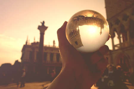 This picture was taken at St Marks Square, Venice, Veneto, northeastern Italy. Sunset was coming. It was spring. The portrays a hand holding a transparent glass ball reflecting an upside down image of some of St Marks Square, the monuments of Partes Doges Palace, National Library of St Mark  ,  s, respectively). The Column of San Marco is also included. Venice is a very popular holiday destination and is famous for its history, art and gothic architecture. Stock Photo