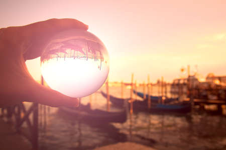 This picture was taken at St Marks Square, Venice, Veneto, northeastern Italy. Sunset was coming. It was spring. It is a portrays to a perfectly transparent glass ball reflecting an upside-down image of the Grand Canal, and the Venetian Lagoon. This part of the Grand Canal is located along St Marks Square. Gondolas, a jetty, streetlights, a water taxi, and part of the pavement are also included.
