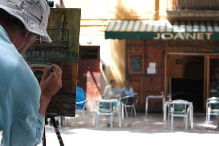Painter doing a portrait of a square with a bar. Barcelona in spring photo
