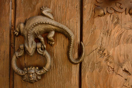 Metal knocker shaped dragon or lizard. Spanish colonial style door. Cartagena de Indias, Colombia.  photo
