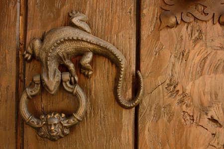knocker: Metal knocker shaped dragon or lizard. Spanish colonial style door. Cartagena de Indias, Colombia.