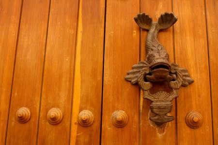 Metal knocker shaped fish. Spanish colonial style door. Cartagena de Indias, Colombia.  photo