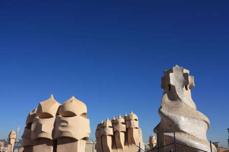 anthropomorphic: On the terrace of the Casa Mila (also called La Pedrera) is a cross-shaped chimneys and soldiers of anthropomorphic forms created by Antonio Gaudi. It was created in 1905. Photo background. Stock Photo