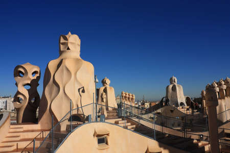 On the terrace of the Casa Mila (also called La Pedrera) is a cross-shaped chimneys and soldiers of anthropomorphic forms created by Antonio Gaudi. It was created in 1905. Photo background. photo