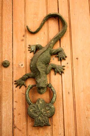 Metal knocker shaped dragon or lizard. Spanish colonial style door. Cartagena de Indias, Colombia.  photo