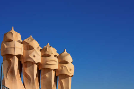 Barcelona & Gaudi. On the terrace of the Casa Mila (also called La Pedrera) is a cross-shaped chimneys and soldiers of anthropomorphic forms created by Antonio Gaudi. It was created in 1905. Photo background. Stock Photo