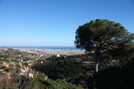 Overview of Barcelona from Collserola mountain, with the Mediterranean Sea in the background. One can observe the Agbar Tower, La Sagrada Famila or Maphre towers. photo