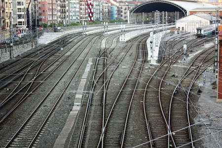 Railroad tracks and catenary, with crossings of roads and sidewalks. Bilbao, Spain. Stock Photo - 7461736